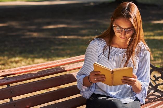 Schöner schuss eines mädchens in einem blauen hemd und mit der brille, die ein buch auf der bank liest