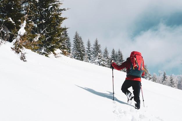 Schöner schuss eines männlichen wanderers mit einem roten reiserucksack, der auf einem schneebedeckten berg im winter wandert