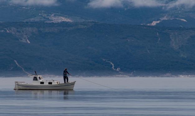 Schöner schuss eines mannes auf einem boot, das fisch im see mit bergen im hintergrund fängt