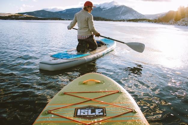 Schöner schuss eines mannes, der auf einem paddleboard sitzt, das ein ruder mit bergen hält