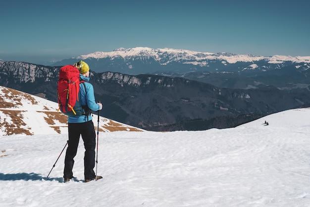 Schöner schuss eines mannes, der in den schneebedeckten karpaten in rumänien wandert