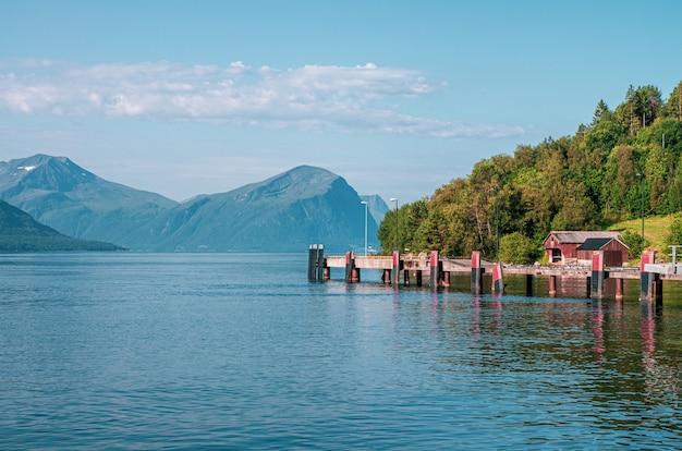 Schöner schuss eines piers auf dem meer nahe einem baumwald, der durch hohe berge in norwegen umgeben ist