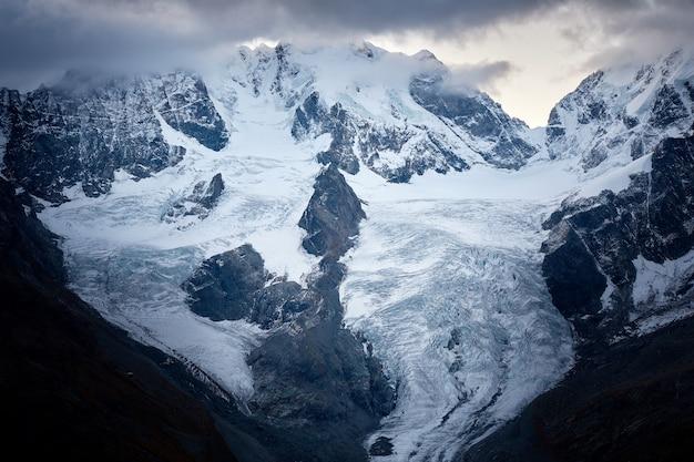 Schöner schuss eines schneebedeckten berges unter einem bewölkten himmel