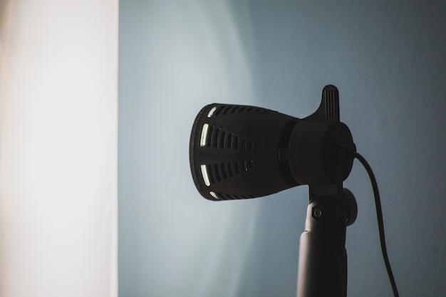Schöner schuss eines schwarzen bühnenlichts mit einer blauen wand