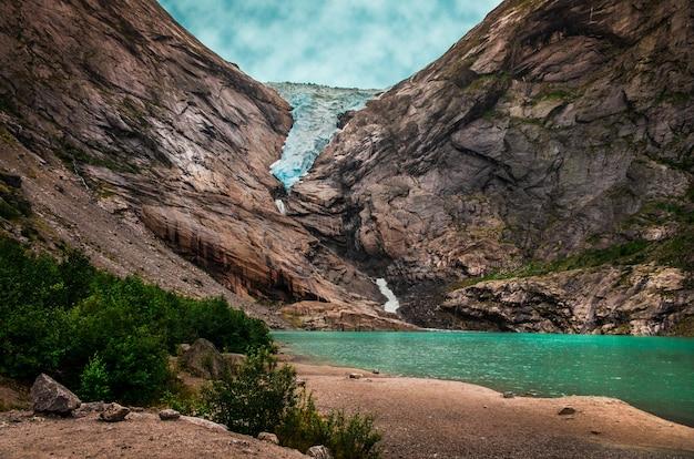 Schöner schuss eines sees nahe hohen felsigen bergen unter dem bewölkten himmel in norwegen