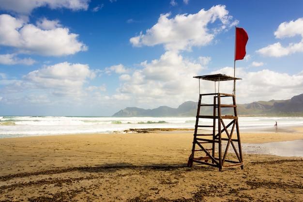 Schöner schuss eines strand-rettungsschwimmer-sitzes mit einer roten fahne in mallorca