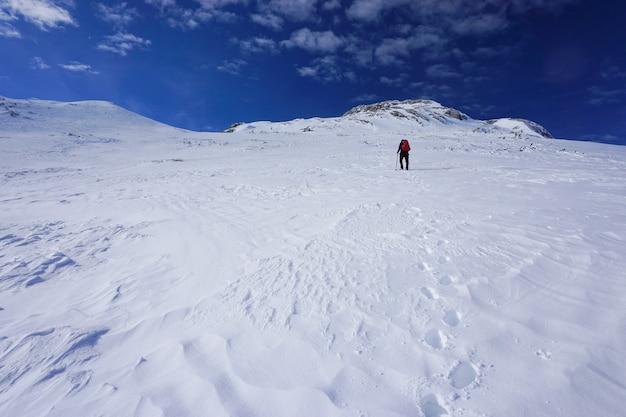 Schöner schuss eines wanderers mit einem roten reiserucksack, der einen berg unter dem blauen himmel wandert