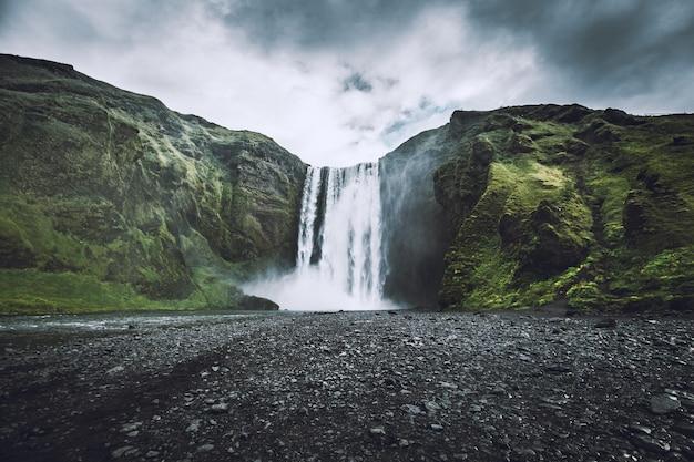 Schöner schuss eines wasserfalls, der von den bergen herabkommt