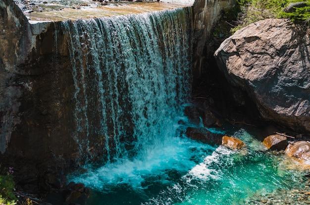 Schöner schuss eines wasserfalls nahe riesigen felsformationen in pragelato, italien