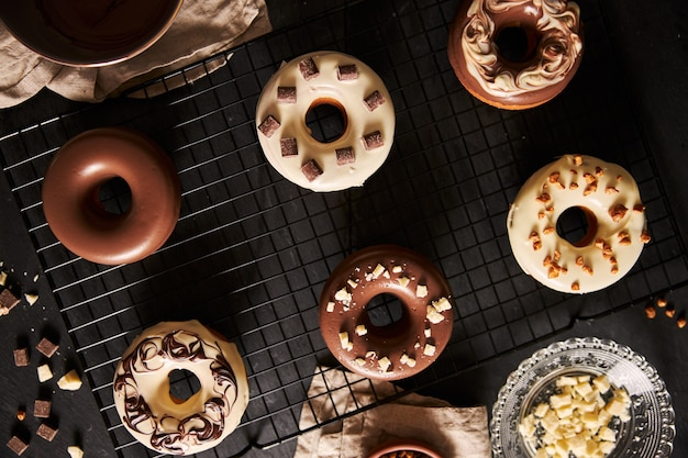 Schöner schuss von köstlichen donuts bedeckt in der glasur und in den schokoladenstücken auf einem schwarzen tisch