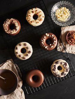 Schöner schuss von köstlichen donuts bedeckt in der schokoladenglasur mit den zutaten auf einem tisch