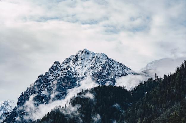 Schöner schuss von nebligen und wolkigen hohen felsigen bergen