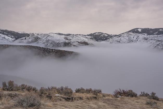 Schöner schuss von schneebedeckten bergen über dem nebel mit einem bewölkten himmel