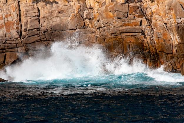 Schöner schuss von starken meereswellen, die auf die klippe schlagen