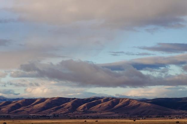 Schöner schuss von steilen hügeln einer wüste mit erstaunlichem bewölktem himmel