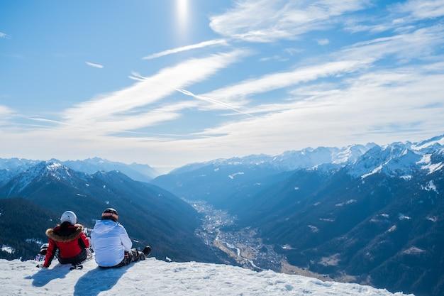 Schöner schuss von zwei personen, die tagsüber die aussicht auf berge und tal genießen