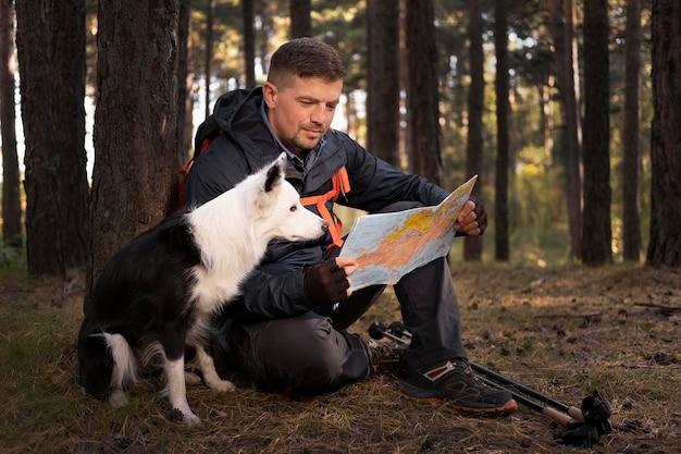 Schöner schwarzweiss-hund, der eine karte betrachtet