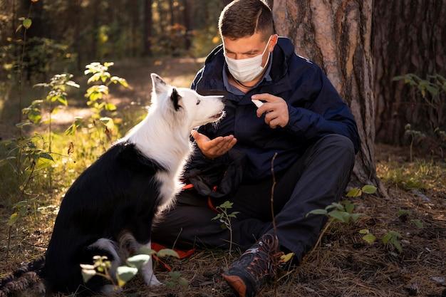 Schöner schwarzweiss-hund und mann, die maske tragen