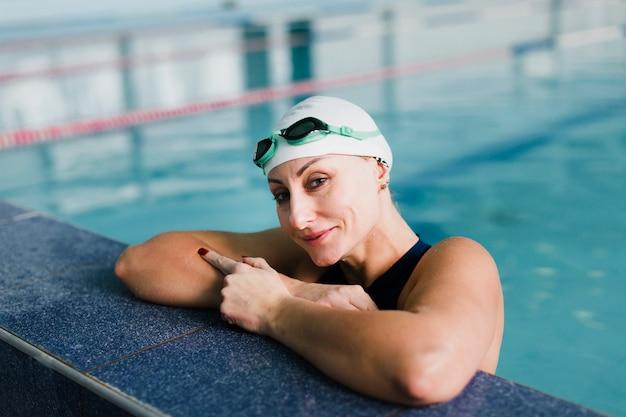Schöner schwimmer, der im swimmingpool sich entspannt