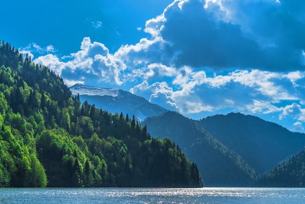 Schöner see ritsa im kaukasus. grüne berghügel, blauer himmel mit wolken. frühlingslandschaft.
