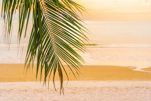 Schöner seeozeanstrand mit palme zur sonnenaufgangzeit für feiertag