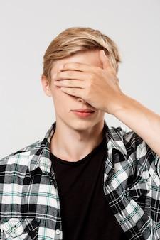 Schöner selbstbewusster blonder junger mann, der lässiges kariertes hemd trägt, das augen mit hand bedeckt, auf grauer wand