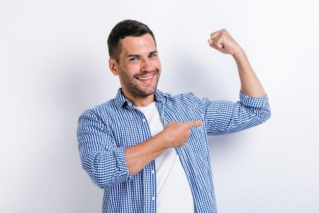 Schöner selbstbewusster mann, der mit dem finger auf seinen armmuskel zeigt, im fitnessstudio pumpt, rabatt. indoor-studioaufnahme isoliert auf weißem hintergrund