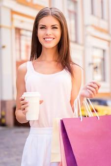 Schöner shopaholic. schöne junge lächelnde frau, die einkaufstüten und eine tasse heißes getränk hält, während sie im freien steht