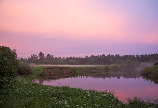 Schöner sommerrosa-abendsonnenuntergang auf dem fluss