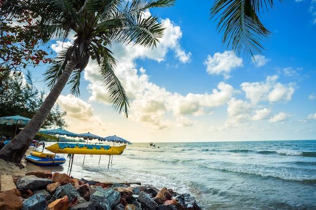Schöner sonnenaufgang des frühen morgens über bananenboot legt unter kokosnussbaum
