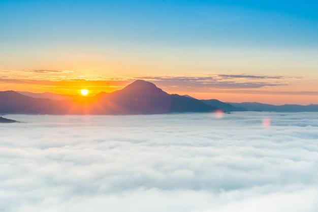 Schöner sonnenaufgang über berg mit nebel morgens