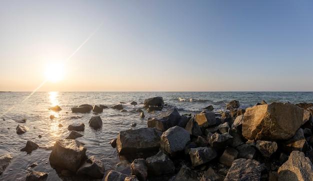 Schöner sonnenaufgang über den meervordergrundsteinhintergründen