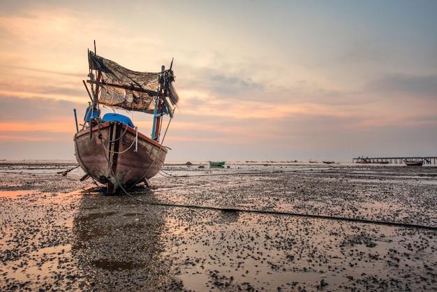 Schöner sonnenaufgang über einem alten hölzernen fischerboot auf thailand-strand