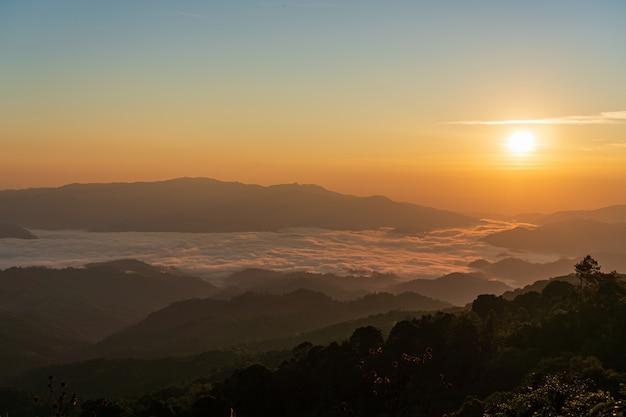 Schöner sonnenaufgang und bunter himmel im nebel über dem berg