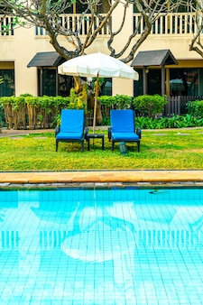 Schöner sonnenschirm und stuhl rund um den pool im hotel und resort