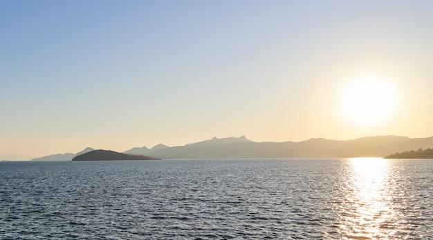 Schöner sonnenuntergang am mittelmeer mit inseln und bergen