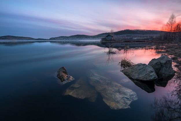 Schöner sonnenuntergang auf dem see mit einem strukturierten vordergrund