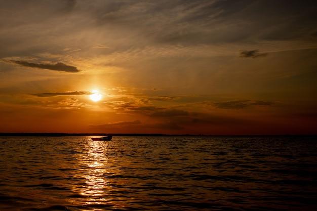 Schöner sonnenuntergang auf dem see mit wolken und reflexionen auf dem wasser.