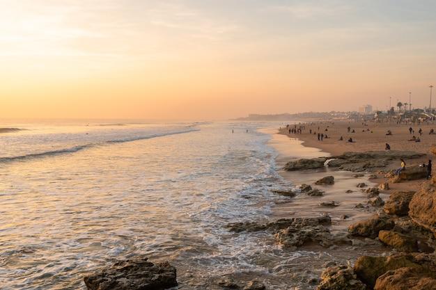 Schöner sonnenuntergang im atlantik in portugal und familien, die an einem sonnigen tag am strand genießen