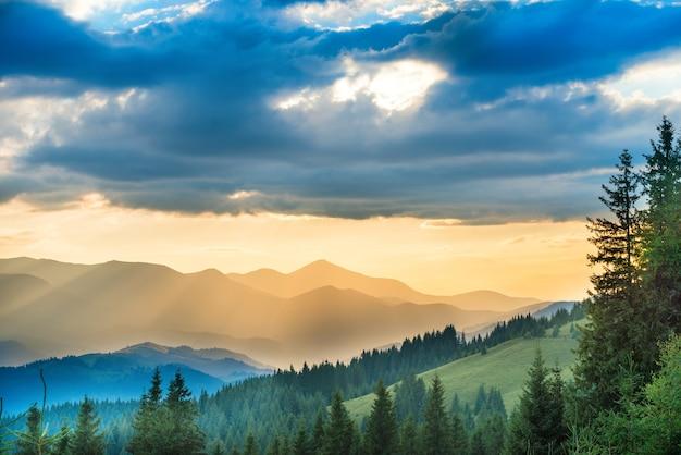 Schöner sonnenuntergang in den bergen. landschaft mit sonne, die durch orangefarbene wolken scheint