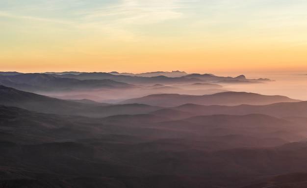 Schöner sonnenuntergang in den krimbergen, krim. majestätischer sonnenuntergang in den bergen gestalten mit sonnigen strahlen landschaftlich.