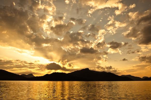 Schöner sonnenuntergang mit berg über dem meer