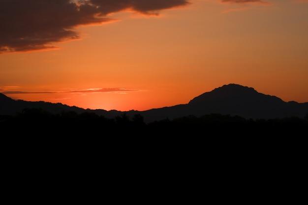 Schöner sonnenuntergang mit bergen mit orangefarbenem horizont in mae sot, thailand.
