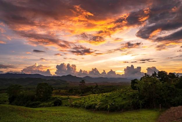 Schöner sonnenuntergang mit bergen mit orangefarbenem horizont.