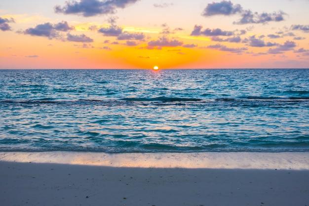 Schöner sonnenuntergang mit himmel über ruhigem see in der tropischen malediven-insel.