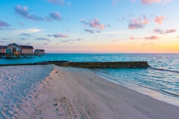 Schöner sonnenuntergang mit wasserlandhäusern in der tropischen malediven-insel.