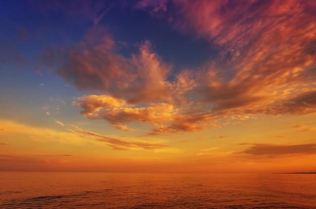 Schöner sonnenuntergang, morgendämmerung, über dem meer, ozean, vor dem hintergrund des blauen himmels und der bunten wolken