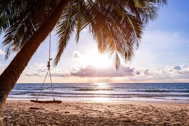Schöner sonnenuntergang oder sonnenaufgang mit schattenbildpalme auf tropeninsel