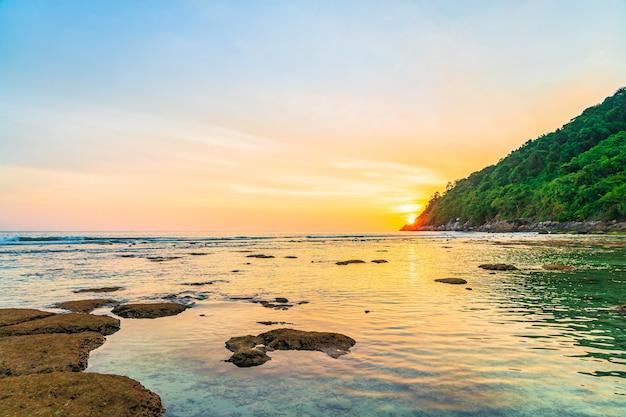 Schöner sonnenuntergang über berg um strandmeerozean und felsen