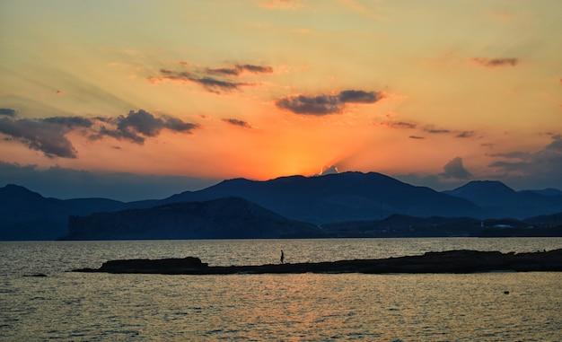 Schöner sonnenuntergang über dem berg und dem meer und einer person